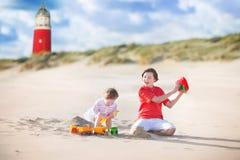 海滩的迷人的兄弟姐妹在灯塔旁边 免版税库存照片