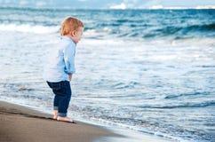 海滩的逗人喜爱的男婴,敬佩海 赤脚 愉快 免版税库存照片