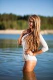 海滩的长的头发妇女在一件短的白色礼服 库存照片