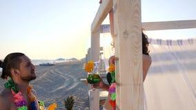 海滩的,女孩恋人在度假穿戴脖子的夏威夷列伊人,夫妇,饮料鸡尾酒和佩带的项链 股票视频