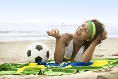 海滩的年轻可爱的女孩与巴西旗子和橄榄球 免版税图库摄影