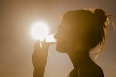 海滩的年轻可爱的妇女在日落喝从玻璃的 库存照片
