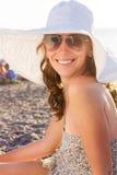 海滩的年轻微笑的妇女在海附近 免版税库存图片