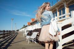 海滨的年轻快乐的女孩 步行的年轻美丽的金发碧眼的女人,愉快 库存照片