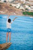 海滩的年轻愉快的女孩有老小村庄惊人的看法在米科诺斯岛,希腊语 免版税图库摄影