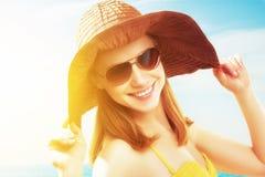 海滩的年轻愉快的妇女在太阳镜和帽子 免版税图库摄影