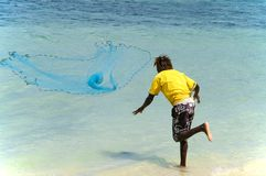 海滩的年轻毛里求斯人把网扔出去钓鱼 库存照片