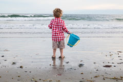 海滩的年轻男孩与在日落的蓝色桶 库存图片