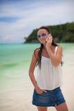 海滩的年轻美丽的妇女谈话在她 免版税库存照片