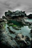 海水看法在岩石顶部的在一多云天 库存图片