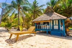 海滩睡椅、清楚的水和美丽的景色在热带海岛上, 免版税库存图片