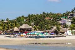 海滩睡椅和伞在埃斯孔迪多港在背景中靠岸,与一个好的绿色森林,墨西哥 免版税库存照片