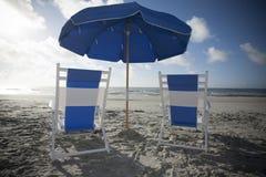 海滩睡椅和伞在海洋 免版税库存图片