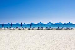 海滩睡椅和伞在白色沙子海靠岸 免版税库存照片