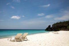 海滩睡椅和天蓝色的蓝色海 免版税库存图片