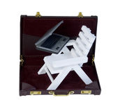 海滩睡椅和膝上型计算机在公文包 图库摄影