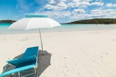 海滩睡椅和遮阳伞在一个热带海滩 免版税库存照片