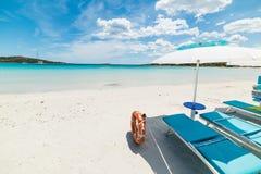 海滩睡椅和遮阳伞由海 免版税库存照片