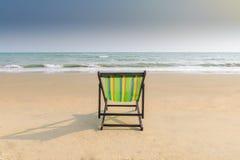 海滩睡椅和阴影在白色沙子靠岸与日落光天空 免版税图库摄影