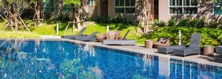 海滩睡椅和sunbeds临近游泳池 免版税库存图片