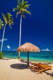 海滩睡椅在有棕榈树的,萨摩亚海岛伞下 库存图片