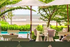 海滩睡椅在热带庭院和海里 免版税库存图片
