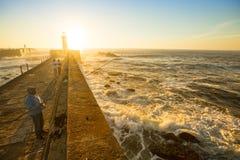 海洋石头码头的渔夫 免版税图库摄影