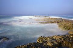 海洋礁石用打旋的水 免版税库存图片