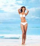 海滩背景的一名年轻深色的妇女 免版税库存图片