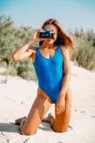 海滩英国概念节假日护照夏天玩具 比基尼泳装射击的微笑妇女与在热带白色沙子海滩的老减速火箭的照相机 性感的夏天妇女身体 免版税图库摄影