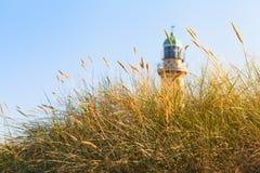 海滩草和灯塔在阳光下 免版税库存图片