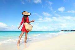 海滩装妇女走与太阳帽子的和海滩请求 免版税库存图片