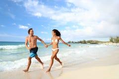 海滩跑在度假的暑假夫妇 免版税库存照片