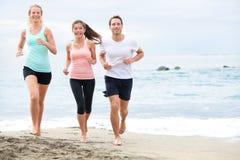 海滩跑步的连续朋友 免版税库存照片
