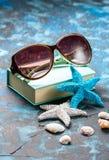 海滩辅助部件 贝壳、太阳镜和海星在深蓝背景 复制空间 旅行和冒险概念 库存照片
