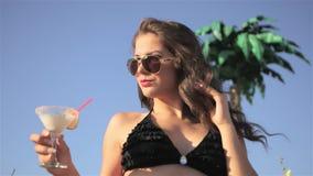 海滩酒吧的摆在年轻美丽的性感的女孩在有鸡尾酒的比基尼泳装在日落喝和 影视素材