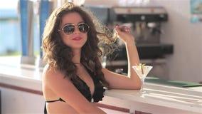 海滩酒吧的摆在年轻美丽的性感的女孩在有鸡尾酒的比基尼泳装在日落喝和 股票视频