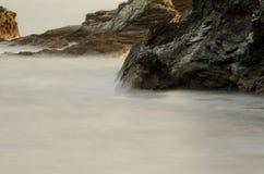 海洋水长的曝光在岩石海岸的在峭壁的基地 免版税库存照片