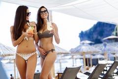 海滩饮用的鸡尾酒的美丽的妇女 免版税库存图片