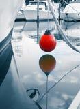 海洋bouy垂悬水面上在被停泊的小船之间在Tutukaka 免版税库存图片