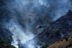 浸入在Sayalonga和竞技场,西班牙之间的野火的Junta De安达卢西亚直升机响铃212采取的水 免版税库存图片