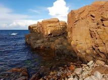 浸泡下来入蓝色海洋的带红色峭壁在Hovs Hallar,瑞典,一个晴天 免版税库存图片