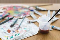 浸泡在水的油漆刷在桌上的 库存照片