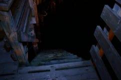 浸泡导致下来海平面的木码头楼梯在晚上 库存照片