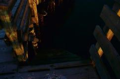 浸泡导致下来海平面的木码头楼梯 免版税库存照片