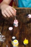 浸洗在一个瓶子的一把刷子油漆 掠过在创作者的手上 免版税库存图片