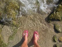 浸洗脚趾的夫人对浅海水渐近佩带的触发器 库存图片