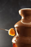 浸洗甜瓜球入巧克力涮制菜肴 免版税图库摄影