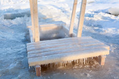 浸洗的木扶手栏杆在冰漏洞水中 免版税库存图片