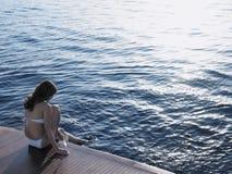 浸洗脚的妇女在海,当坐游艇的地板时 免版税库存照片